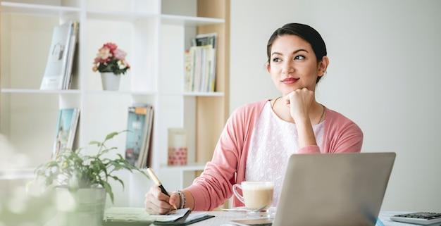 Zelfverzekerde zakenvrouw glimlachend en denkend zittend in een modern kantoor.