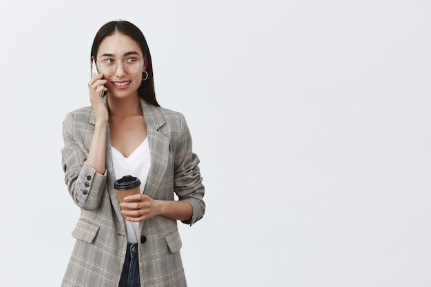 Zelfverzekerde zakenvrouw in jas en bril, die er goed uitziet met een geïntrigeerde en vreugdevolle uitdrukking terwijl ze een smartphone gebruikt en koffie drinkt