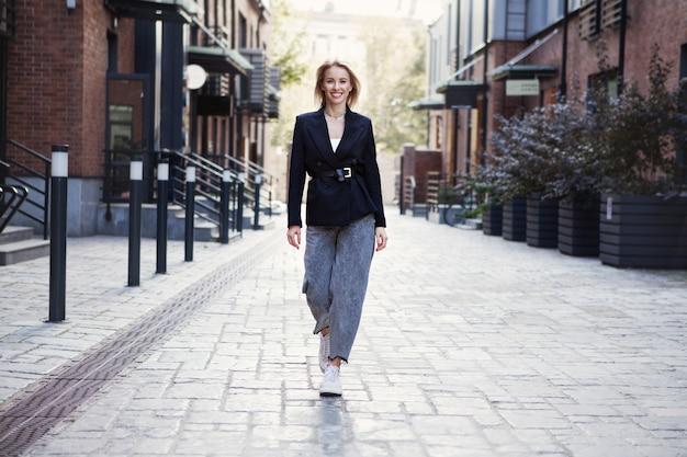 Zelfverzekerde zakenvrouw in stijlvolle kantoorkleding wandelen stad straat mooie lachende vrouw gaan werken dragen stijl modieuze lente of herfst zwarte jas oversized slouchy jeans buitenshuis