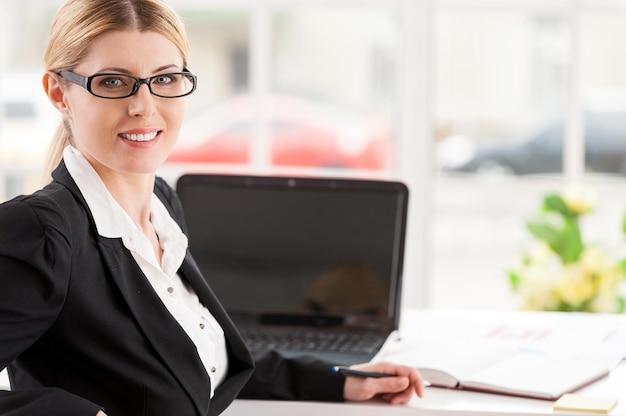 Zelfverzekerde zakenvrouw. mooie rijpe vrouw in formalwear die over de schouder kijkt en glimlacht terwijl ze op haar werkplek zit