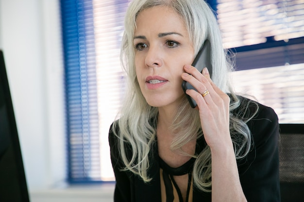 Zelfverzekerde zakenvrouw praten via de telefoon in kantoorruimte en iets te kijken. close-upportret van ceo project op smartphone bespreken. bedrijfs-, communicatie- en topmanagementconcept