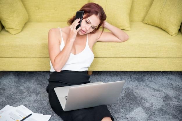 Zelfverzekerde zakenvrouw thuis praten over de telefoon