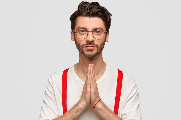 Zelfverzekerde, zelfverzekerde, bebaarde jonge man houdt de handen in het biddende gebaar, draagt een witte trui met rode beugels, heeft een serieus gezicht, gelooft in beter. aantrekkelijke jonge man heeft vertrouwen in beter