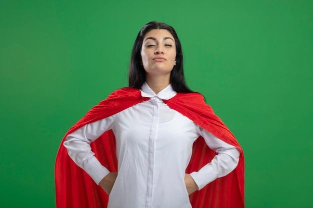 Zelfvoldane jonge kaukasische superheld meisje hand in hand op de heupen met half gesloten ogen kijken camera geïsoleerd op groene achtergrond met kopie ruimte