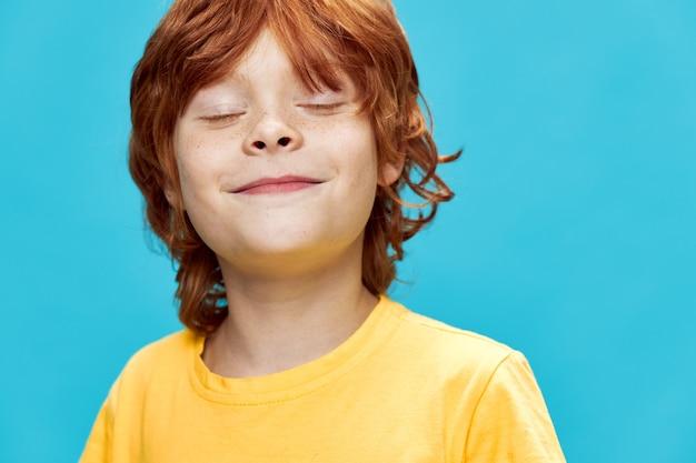 Zelfvoldane roodharige jongen in geel t-shirt op blauwe achtergrond met gesloten ogen