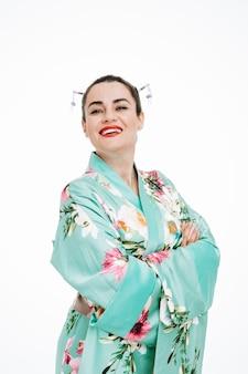 Zelfvoldane vrouw in traditionele japanse kimono met grote glimlach op haar gezicht met gekruiste armen op haar borst op wit