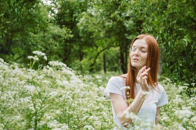 Zelfzorg, geestelijk welzijn, geestelijke gezondheid, mindfulness. jonge roodharige vrouw genieten van het leven in de natuur tussen bloemen en groene bomen.