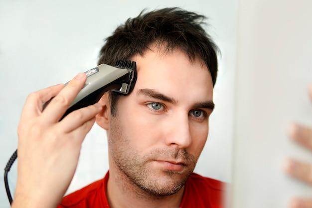 Zelfzorg in de omstandigheden van wereldwijde quarantaine en gesloten kappers en schoonheidssalons. knappe man knipt zijn eigen haar met een tondeuse en kijkt in de spiegel. zelf opruimen.