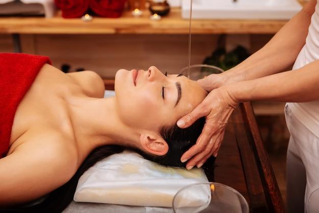 Zelfzorg routine. aantrekkelijke naakte vrouw wordt bedekt met een rode handdoek tijdens de procedure in een professioneel spa-centrum towel