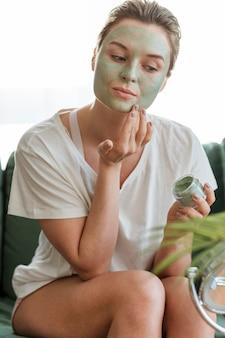 Zelfzorg thuis met vrouw die gezichtsmasker toepast