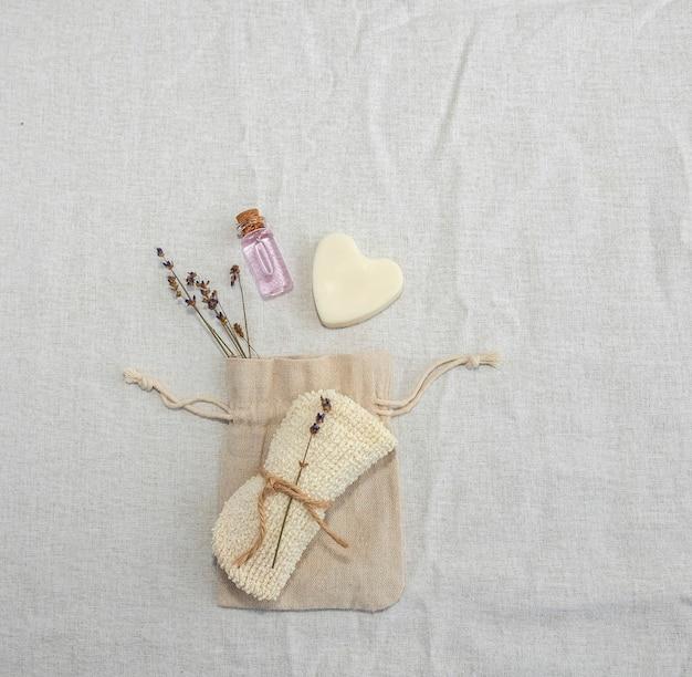Zelfzorgaccessoires in het zero-weist-concept. op linnen stof, een linnen tas, lavendelzakje, zelfgemaakte hartvormige zeep en essentiële lavendelolie.