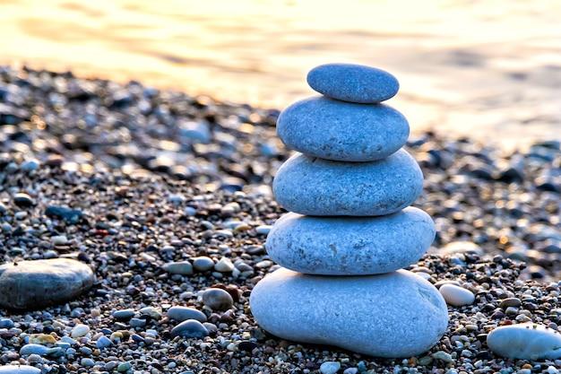 Zen-achtige stenen piramide op het strand bij het aanbreken van de dag
