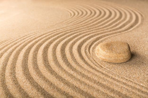 Zen steen in het zand op achtergrond