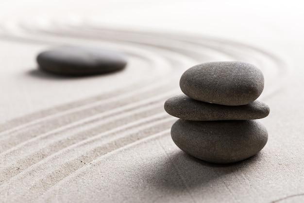 Zen-steentuin rond steen en geharkt zand