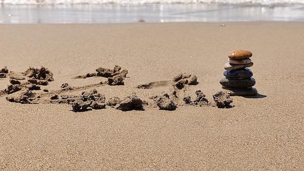 Zen stenen aangelegd met de hand liggend op zand van zee strand. zomervakantie