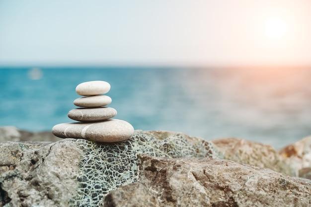 Zen-stenen zijn achtergrond een piramide van kiezelstenen tegen de achtergrond van de lucht, zee en strand