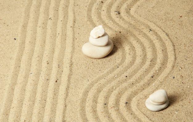 Zen-tuin met geharkt zand en ronde stenen close-up