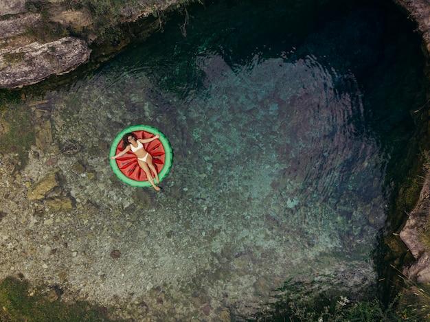 Zenithal mening van een meisje die in een watermeloenvlotter ontspannen dichtbij een klip