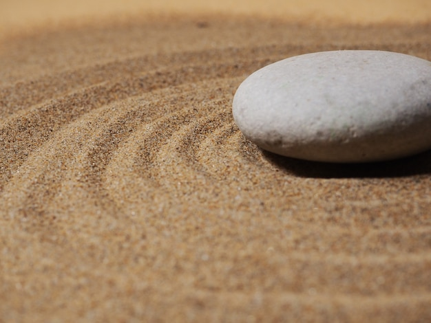 Zentuin. piramides van witte en grijze zenstenen op het witte zand met abstracte golftekeningen.