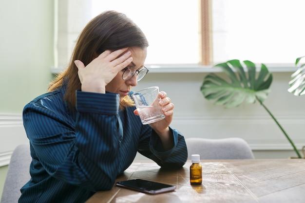 Zenuwaandoening, depressie, nervositeit, aan leeftijd gerelateerde gezondheidsproblemen. rijpe vrouw druipende druppels met een glas water, kalmerende medicijnen drinken, thuis in pyjama, kopie ruimte