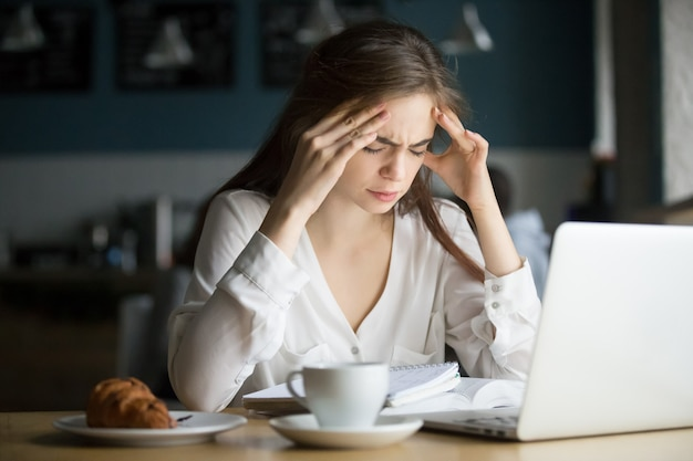 Zenuwachtig beklemtoonde vrouwelijke student die hoofdpijn voelt die in koffie bestudeert