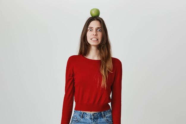 Zenuwachtig meisje met appel op het hoofd en klemmen tanden bang, doelwit van boogschutter