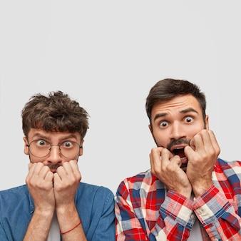 Zenuwachtige aantrekkelijke twee hipsters bijten vingernagels met bezorgde uitdrukkingen, staren met angstige blikken, voelen zich angstig als ze niet slagen voor toelatingsexamen op de universiteit