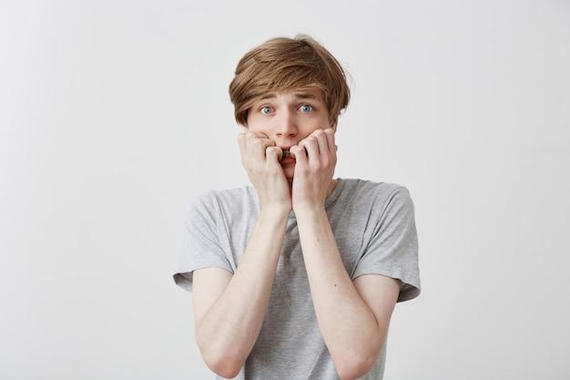Zenuwachtige, angstaanjagende europese man met blond haar en blauwe ogen heeft een afschuwelijke uitdrukking, klemt zijn tanden op elkaar, probeert niet te huilen en ontdekt een tragische gebeurtenis. gestreste mannelijke student voelt zich nerveus voor examens