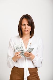 Zenuwachtige vrouw die bezorgd geld tellen