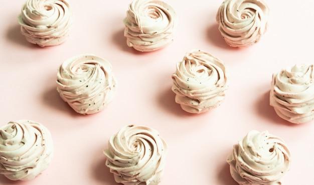 Zephyr in prachtige roze vormen, marshmallow patroon op pastel koraal kleur.