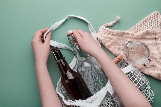 Zero waste boodschappen concept. katoenen tassen en glaswerk. handen verpakking flessen en pot in mesh tas.