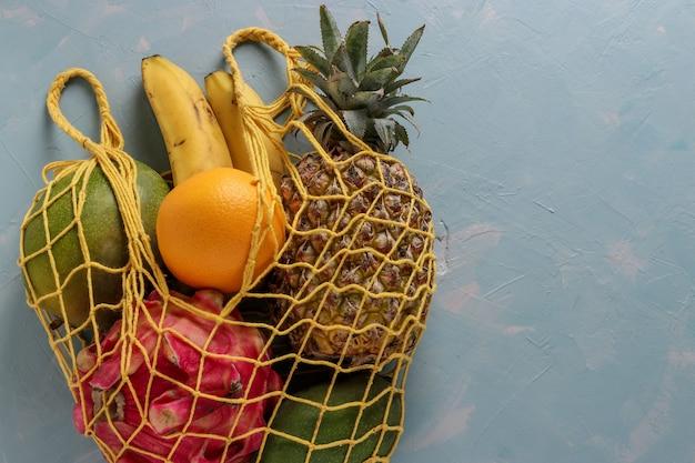 Zero waste concept, mesh stoffen zak met vers tropisch fruit: mango, ananas, dragon, kiwi, banaan en passievrucht op lichtblauw oppervlak, horizontaal formaat