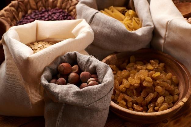 Zero waste-concept. noten, gedroogd fruit, macarons en grutten in eco-katoenen tassen en glazen potten op de houten tafel in de keuken.