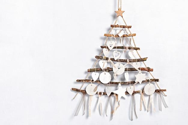 Zero waste kerst met alternatieve handgemaakte kerstboom die over een lichte muur en klei-ornamenten hangt