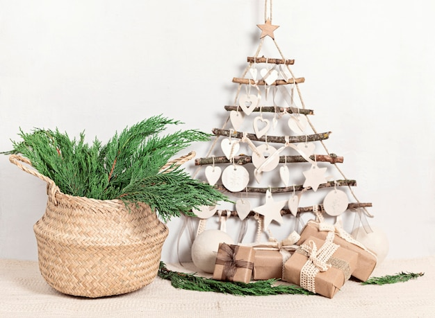 Zero waste kerst met cadeaus verpakt in ambachtelijk papier en alternatieve handgemaakte kerstboom die boven een lichte muur hangt