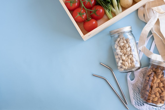 Zero waste lifestyle. katoenen netzak met verse groenten en duurzame glazen pot op blauwe achtergrond