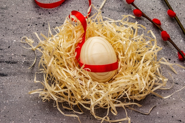 Zero waste pasen concept. houten ei, vogelnest, satijnen lint, rode wilgenzegels. geen plastic, eco-trend. grijze betonnen achtergrond