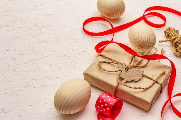Zero waste pasen concept. houten eieren, geschenken in ambachtelijk papier. geen plastic, ecotrend. witte stopverf achtergrond
