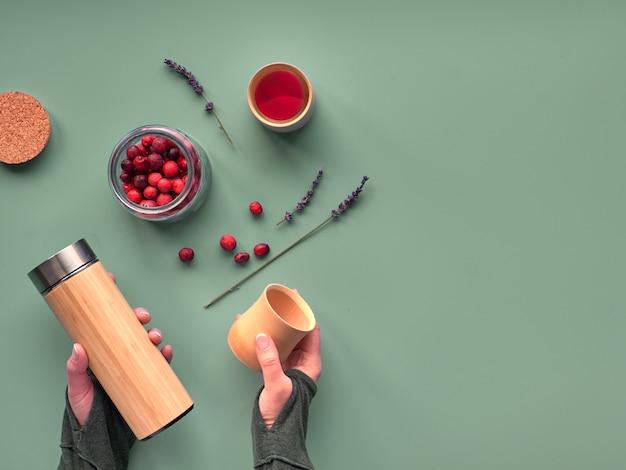 Zero waste tea in reisfles. kruideninfusie maken in milieuvriendelijke geïsoleerde bamboefles met verse cranberrythee. trendy plat lag met handen die de kolf en bamboe bekers vasthielden, kopie-ruimte.