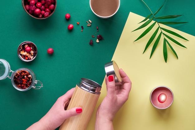 Zero waste tea to go, het maken van kruideninfusie in milieuvriendelijke geïsoleerde bamboe stalen fles met kruidenmengsel en verse cranberry. trendy creatieve plat met handen, tweekleurig groen en geel papier.