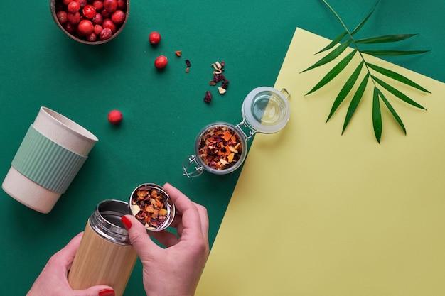 Zero waste tea to go, maakt kruideninfusie in milieuvriendelijke geïsoleerde bamboe stalen kolf met kruidenmengsel en verse cranberry. trendy creatieve plat lag, bovenaanzicht op tweekleurig groen geel papier.