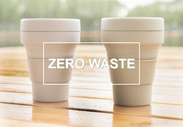 Zero waste tekst op foto van eco herbruikbare bekers op hout