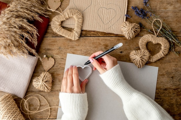 Zero waste valentijnsdag concept. vrouwelijke handen drow stencil hart