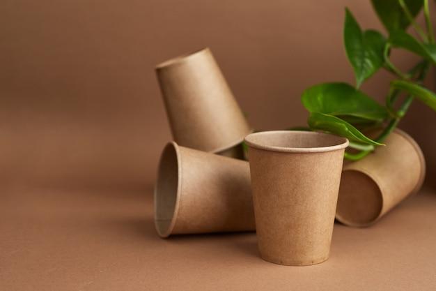 Zero waste. wegwerp papieren bekers met groene bladeren. koffie en ecologie. beige achtergrond