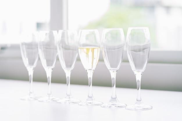 Zes glazen wijn op tafel en slechts 1 met wijn, concept van verschil