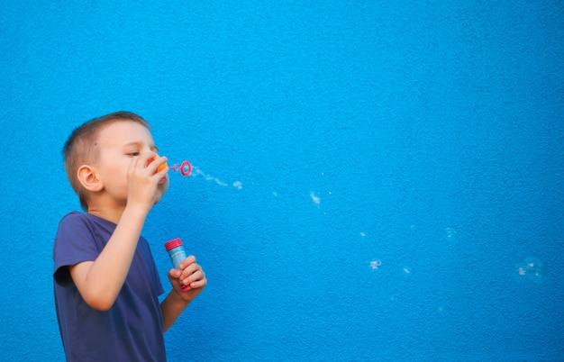 Zes jaar oude jongen met zeepbellen op een blauwe achtergrond