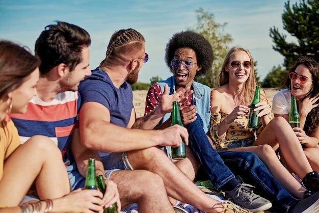 Zes jonge mensen die buiten bier drinken