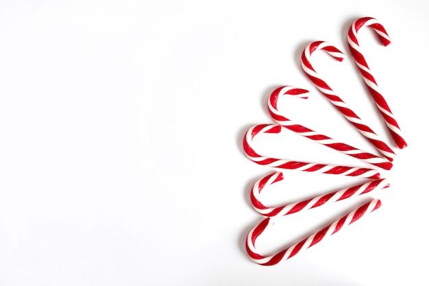 Zes kerstlollys, nieuwjaars rode en witte snoepjes in de vorm van een wandelstok, zijn waaiervormig op een witte achtergrond