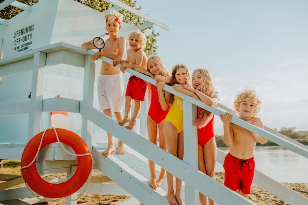Zes kinderen in rode, witte en gele zwemkleding poseren op de badmeestertoren op het strand