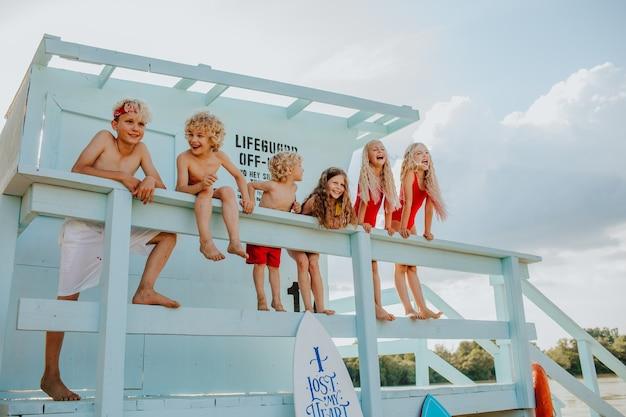 Zes kinderen in zomerkleren poseren op de badmeestertoren op het strand